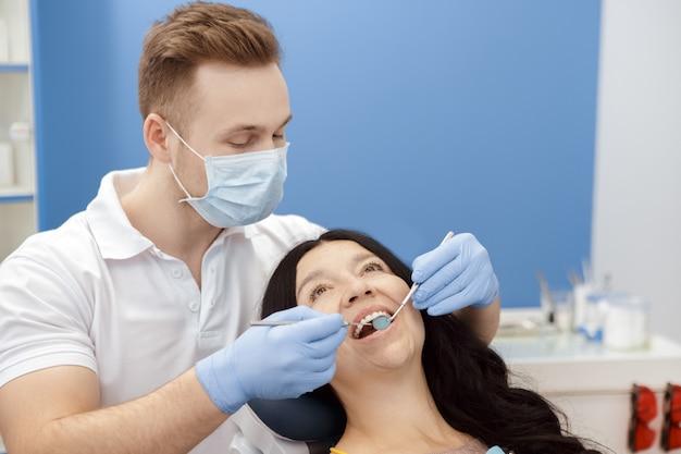 Dentista visitante de mulher sênior na clínica odontológica Foto Premium