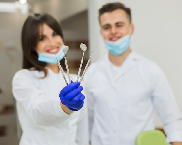 Dentistas desfocados segurando o equipamento dental Foto gratuita