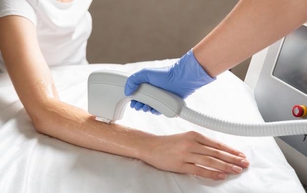 Depilação a laser das mãos em um salão de beleza. procedimento de depilação manual com tecnologia de depilação a laser. Foto Premium