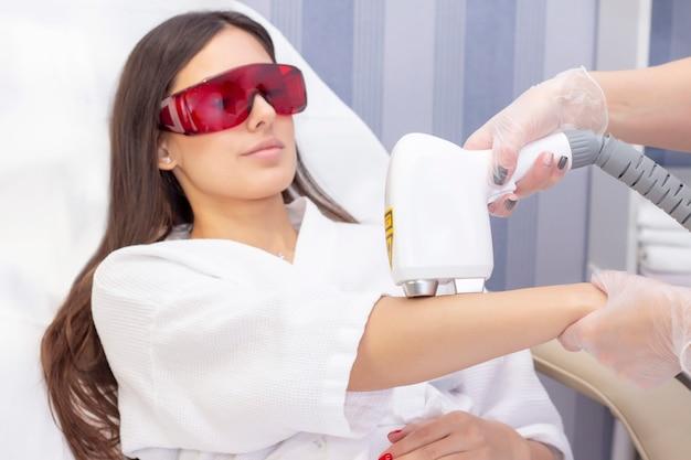 Depilação a laser e cosmetologia. a mulher remove os pêlos do braço com um laser. procedimento de depilação em cosmetologia. depilação a laser e cosmetologia. cosmetologia e conceito de spa Foto Premium
