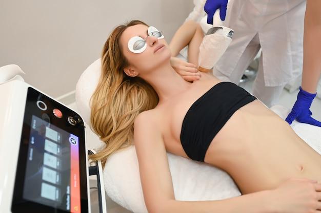 Depilação a laser e cosmetologia em salão de beleza. procedimento de remoção de pêlos. conceito de depilação a laser, cosmetologia, spa e remoção de pêlos. linda mulher loira, cabelo, remoção de axilas Foto Premium
