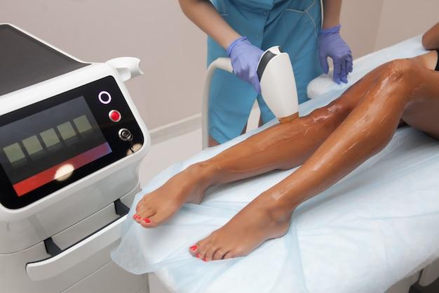 Depilação a laser e cosmetologia em salão de beleza. procedimento de remoção de pêlos. conceito de depilação a laser, cosmetologia, spa e remoção de pêlos. mulher bonita, cabelo, removendo pernas Foto Premium