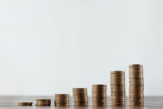 Depósito, moedas na mesa são dispostas em escadas Foto Premium
