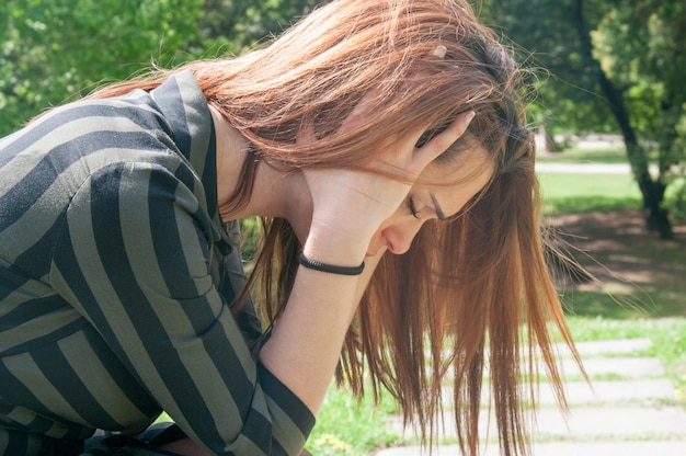 Deprimida garota sentada no banco no parque Foto gratuita