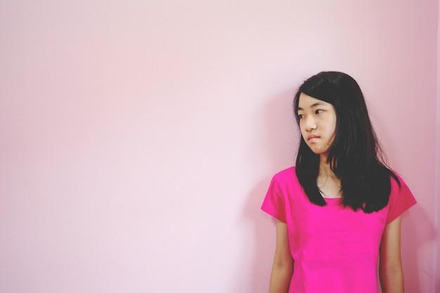 Deprimir e garota desesperada com ausente minded olhando para baixo ficar em fundo rosa Foto Premium