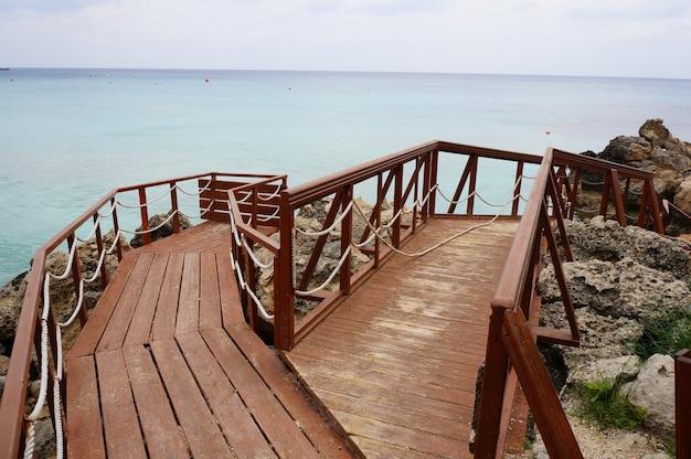 Deque de madeira na costa cercado por rochas e mar sob um céu nublado Foto gratuita