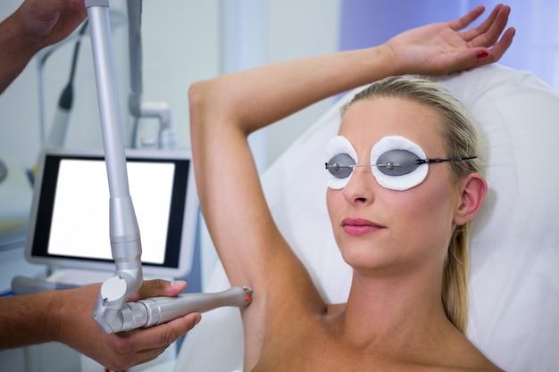 Dermatologista, removendo os pêlos da axila do paciente Foto gratuita
