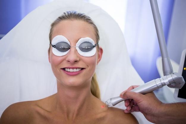 Dermatologista remover toupeira do ombro da mulher Foto gratuita