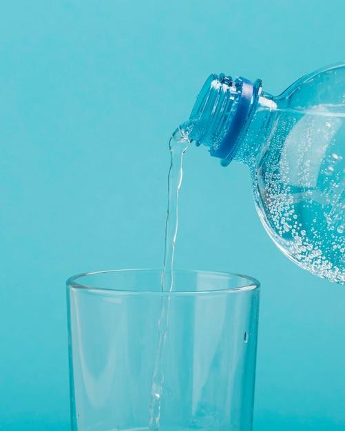 Derramando água com gás de uma garrafa de plástico em um vidro Foto Premium