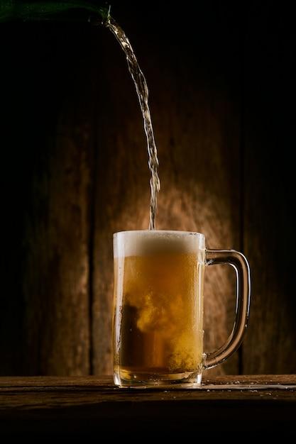 Derramando cerveja no copo Foto Premium