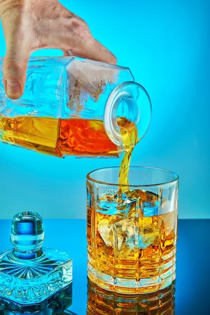 Derramando jarra de cristal quadrado com uísque de fita adesiva ou conhaque em um copo de cristal redondo sobre um fundo gradiente azul com reflexão Foto Premium
