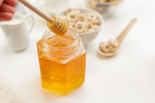 Derramando mel aromático em jarra, closeup Foto Premium
