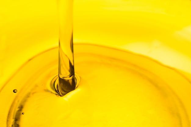 Derramando óleo na tigela, oliva vegetal lubrificante de carro Foto Premium