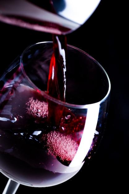 Derramando vinho tinto no copo Foto Premium