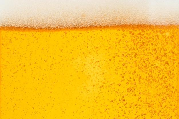 Derramar cerveja com espuma de bolha em vidro para plano de fundo Foto Premium