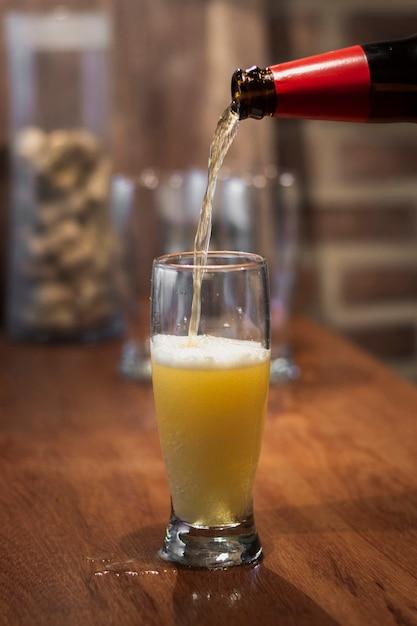 Derramar cerveja de garrafa para cerveja processo Foto gratuita