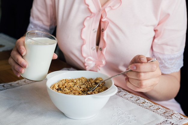 Derramar o leite em uma tigela de muesli Foto Premium