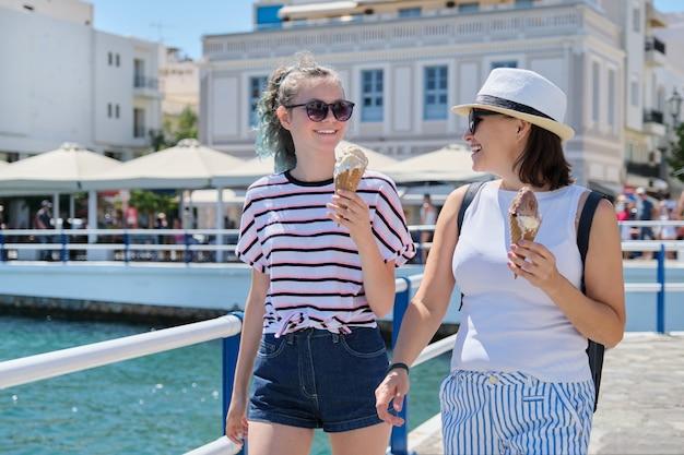 Derretendo sorvete nas mãos de sorrir andando mãe e filha Foto Premium