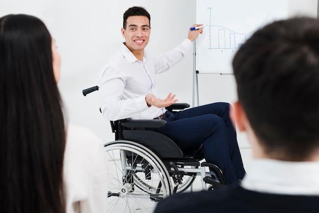 Desativado jovem empresário sentado na cadeira de rodas, dando a apresentação ao seu colega no escritório Foto gratuita