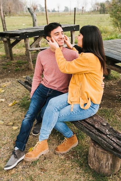 Descansando feliz par se divertindo no banco de madeira no parque outono Foto gratuita