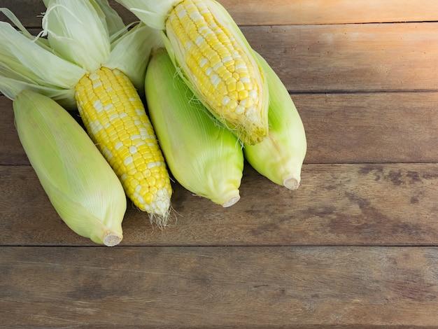 Descascar e descascar o milho cru no fundo da mesa de madeira Foto Premium