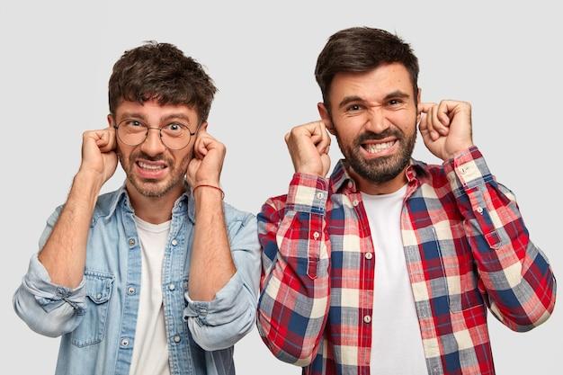 Descontentamento dois caras elegantes tapam os ouvidos com desagrado, cerram os dentes, ignore o barulho alto Foto gratuita