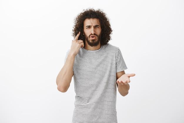Descontente e confuso estudante barbudo de camiseta listrada, apontando para a orelha e franzindo a testa, não consegue ouvir a pergunta enquanto está em alta companhia Foto gratuita