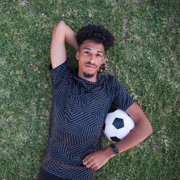 Descontraído desportista deitado de costas durante a pausa no gramado Foto gratuita