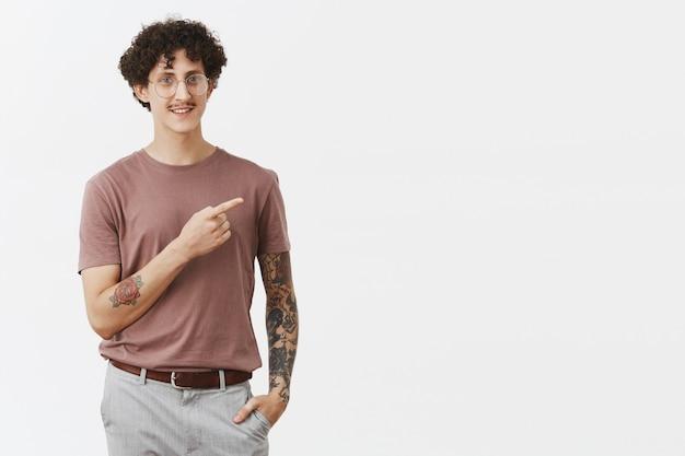 Descontraído e confiante, moderno, elegante, judeu, com bigode de cabelo escuro e encaracolado e tatuagens nos braços apontando para a direita e sorrindo amigável mostrando o caminho ou apontando para um ótimo local Foto gratuita