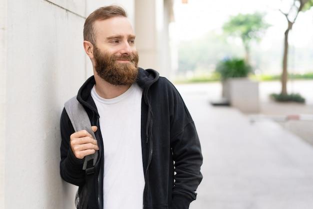 Descontraído jovem barbudo andando na rua Foto gratuita