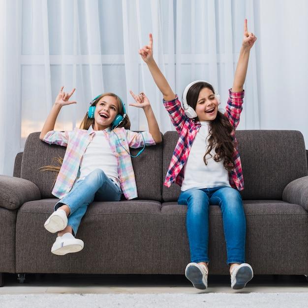 Descontraído lindas duas garotas curtindo a música no fone de ouvido levantando suas mãos dançando Foto gratuita