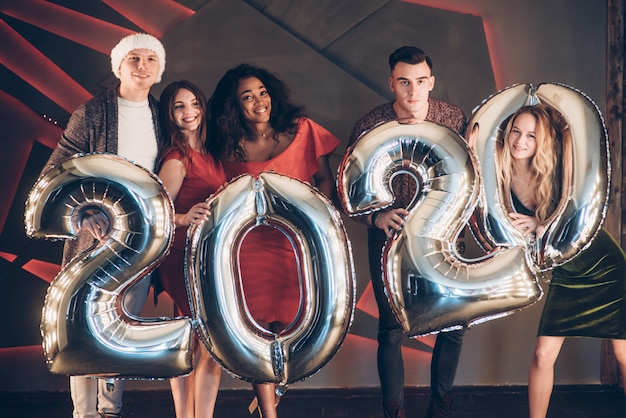 Desejando bem. grupo de jovens amigos lindos com números infláveis nas mãos comemorando o novo ano de 2020 Foto Premium