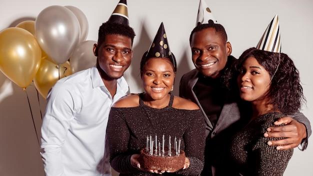 Desejando feliz aniversário e mulher segurando bolo Foto gratuita
