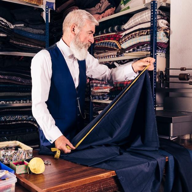 Desenhador moda, medindo, de, azul, tecido, com, medindo fita, ligado, tabela Foto gratuita