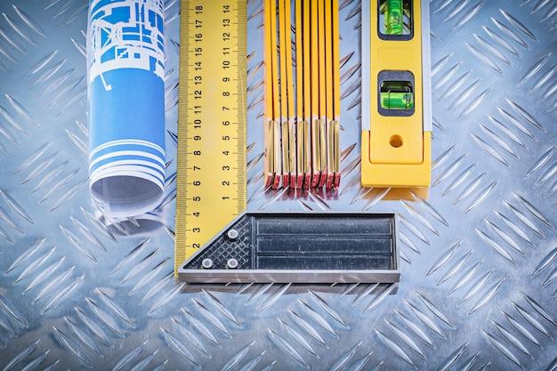 Desenhos de construção nível medidor de madeira tente quadrado sobre fundo de metal ranhurado Foto Premium