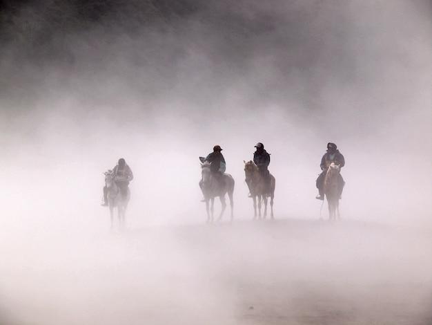 Deserto de bromo e cavaleiros durante a tempestade de areia em bromo Foto Premium