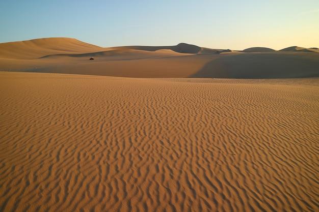 Deserto de huacachina com ondulações de areia bonita e um buggy à distância, ica, peru Foto Premium