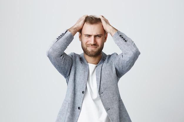 Desesperado irritado irritado homem agarrar a cabeça incomodada Foto gratuita