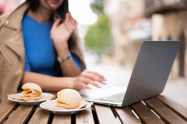 Desfocado mulher trabalhando no laptop fora enquanto almoça Foto gratuita