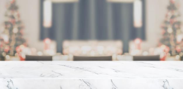 Desfocar a decoração da árvore de natal na mesa da cozinha com sala de estar em mármore Foto Premium