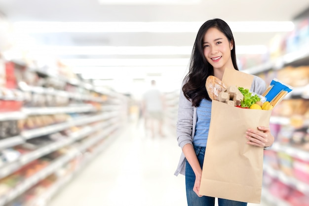 Desfocar a imagem do corredor no supermercado com os clientes Foto Premium