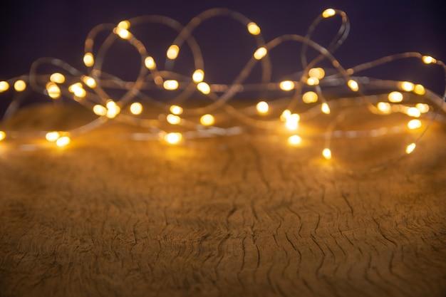 Desfocar as luzes de natal em fundo de madeira. foco seletivo em pranchas de madeira Foto Premium