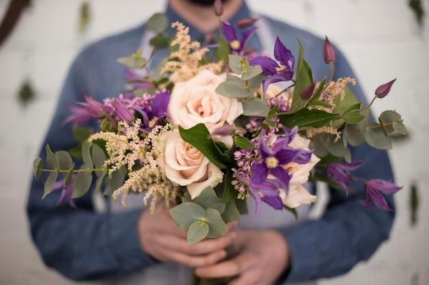 Desfocar florista masculina segurando o buquê de flores na mão Foto gratuita