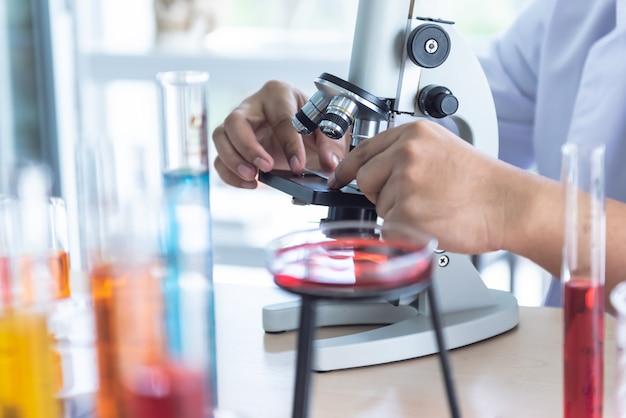 Desfocar imagens suaves do cientista usando um microscópio para inspeção do produto Foto Premium