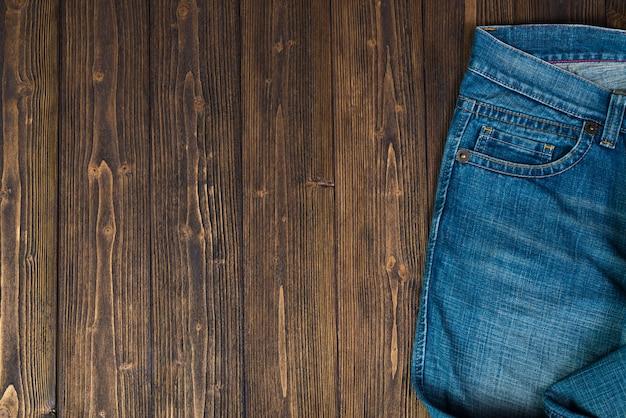Desgastado, jeans ou azul jeans denim coleção no fundo da mesa de madeira escura áspera, vista superior com espaço de cópia Foto Premium