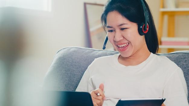 Desgaste casual de mulher de negócios freelance asiáticos usando videoconferência de chamada de trabalho de laptop com o cliente no local de trabalho na sala de estar em casa quando o distanciamento social fica em casa e o tempo de quarentena. Foto gratuita
