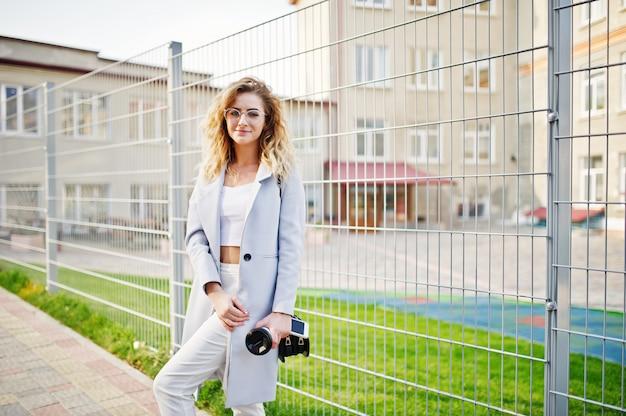 Desgaste de menina modelo loira encaracolado elegante em branco posando contra cerca. Foto Premium