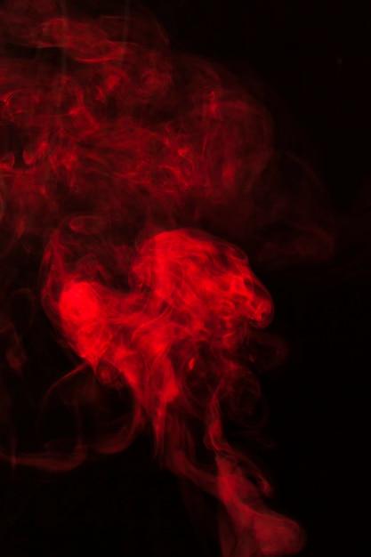 Design de fragmentos de fumaça vermelha sobre um fundo preto Foto gratuita