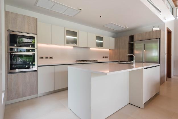 Design de interiores de luxo na área da cozinha, que apresentam balcão ilha e construído em móveis Foto Premium