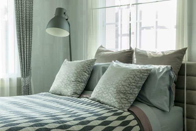 Design de interiores de quarto elegante com almofadas estampadas na cama e candeeiro de mesa decorativo. Foto Premium